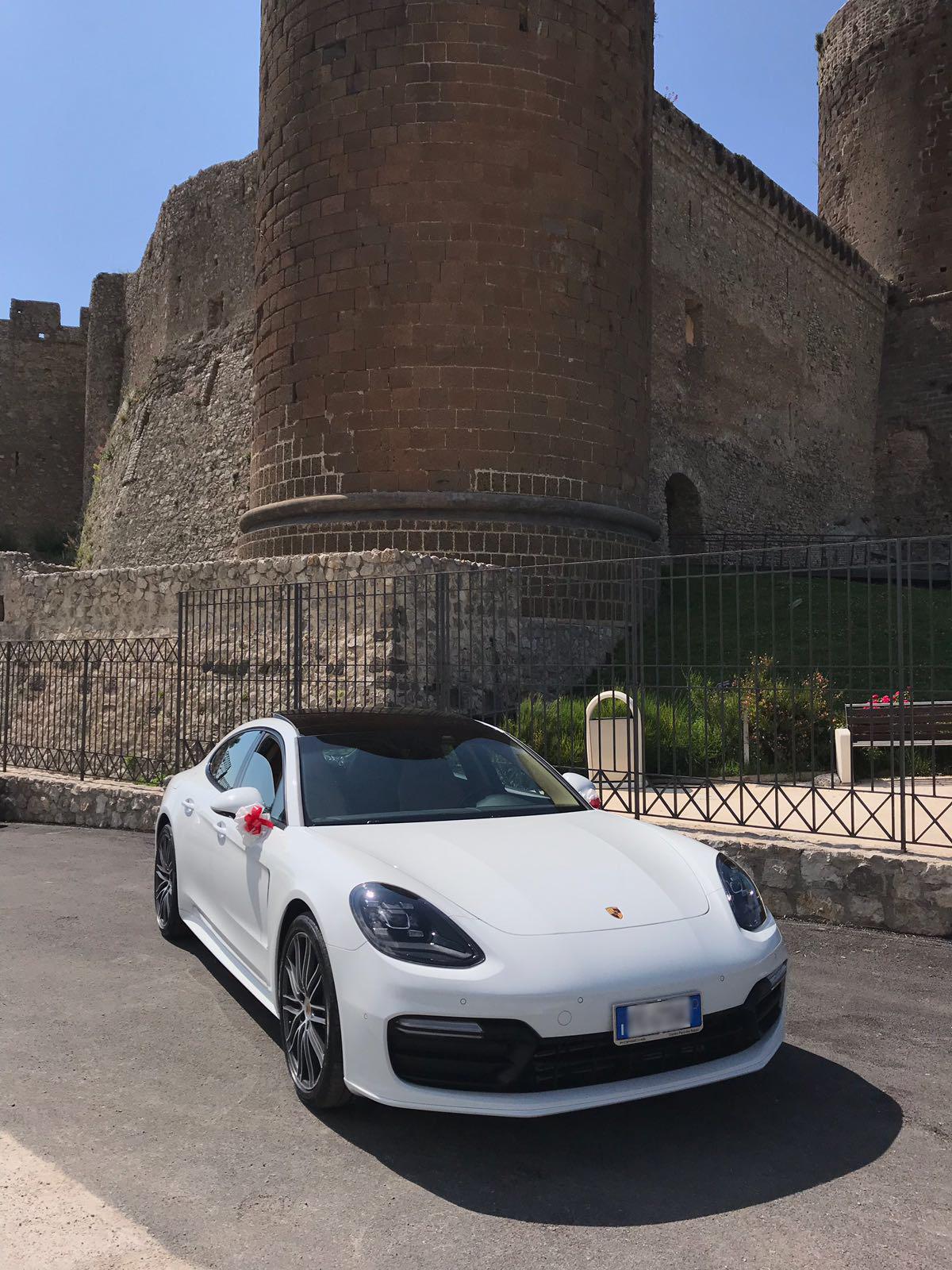 La nuova Porsche panamera con addobbi bianchi e rossi scelto e voluti dagli sposi per mantenere il tema del matrimonio.